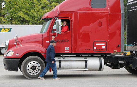 Truck driver trainer helping student drive trucks