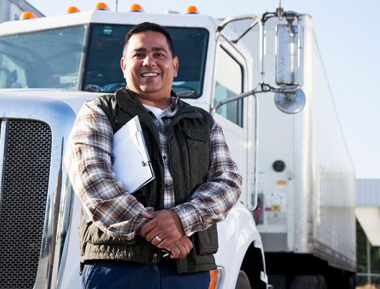 Truck driver standing in front of truck holding a clip board
