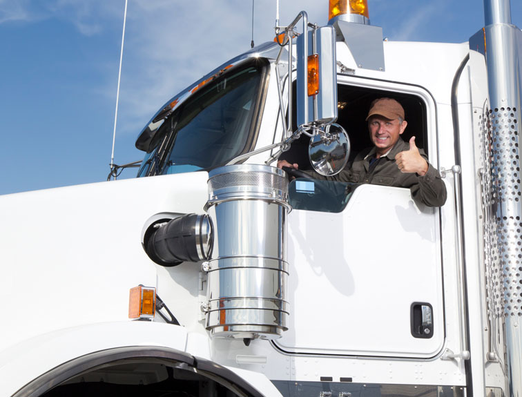 Truck driver with arm out the window of a white rig giving a thumbs up and smiling.